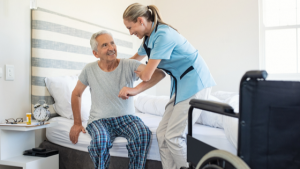 woman nurse offering support to older man getting out of bed
