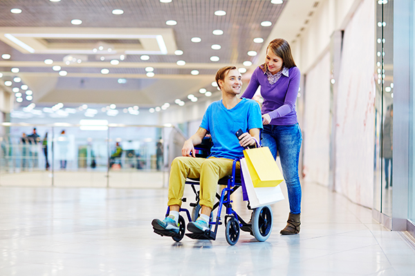 Disabled man and his girlfriend walking in shopping mall
